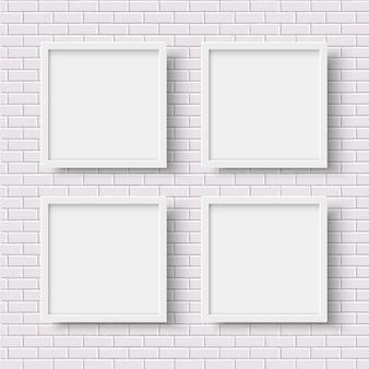 Quatro quadros vazios quadrados brancos na parede de tijolo branco