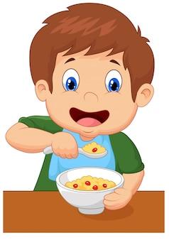 Rapaz está a comer cereais no café da manhã
