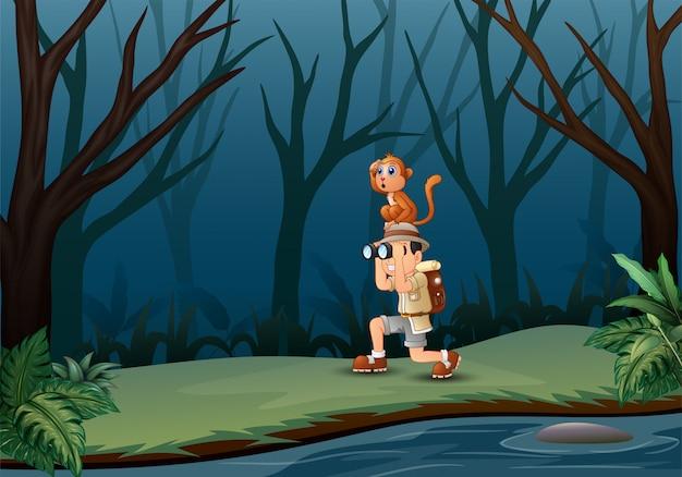 Rapaz, usando binóculos com um macaco na floresta escura