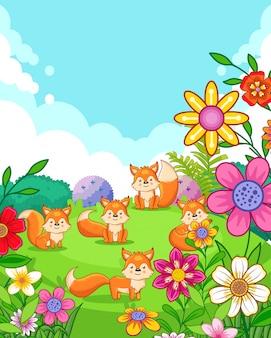Raposas bonitos felizes com as flores que jogam no jardim