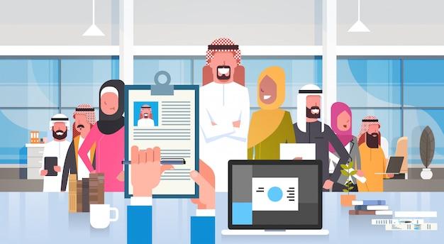 Recrutamento mão segurando currículo escolhendo candidato do grupo de pessoas de negócios árabes no escritório moderno recursos humanos conceito