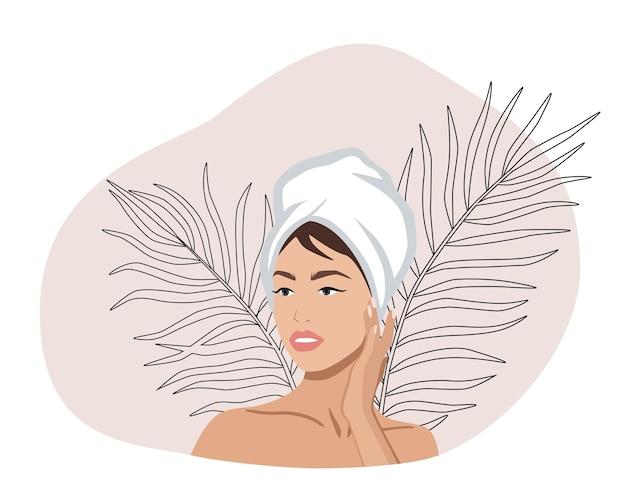 Retrato de uma linda mulher com uma toalha na cabeça tocando seu rosto