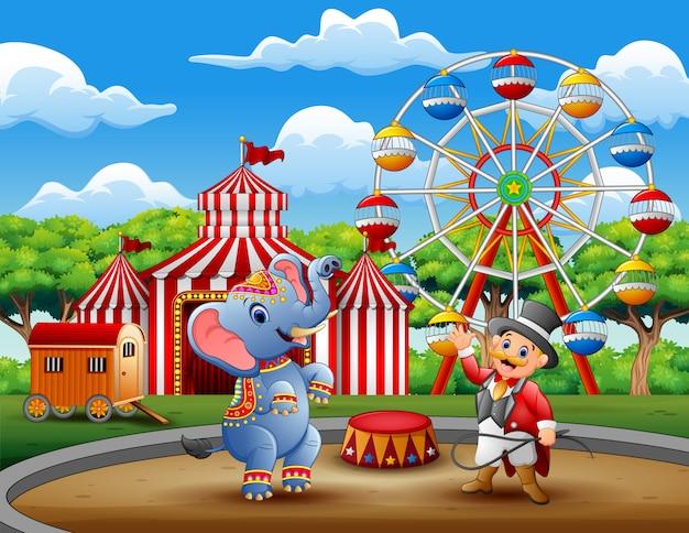 Ringmaster do circo realiza um truque junto com elefante
