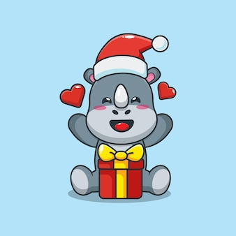 Rinoceronte fofo com chapéu de papai noel com caixa de presente no dia de natal ilustração fofa dos desenhos animados de natal