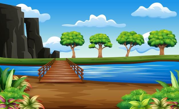 Rio e ponte de madeira em um belo fundo de natureza
