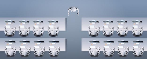 Robô moderno ensinando grupo de robôs humanóides sentado em mesas na escola robótica de sala de aula artificial