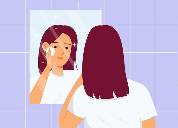 Rotina de cuidados com a pele garota limpando a pele do rosto em frente ao espelho no banheiro