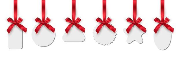 Rótulos de etiquetas em branco de ano novo ou natal com fitas vermelhas se