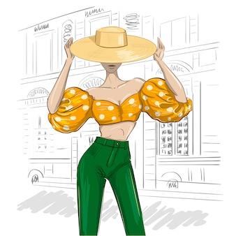 Roupa de mulher linda e ensolarada com chapéu e babados de balão