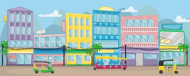Rua asiática com edifícios coloridos, fios elétricos e tuk tuks nas estradas.