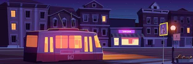Rua da cidade com casas, bonde e estrada vazia com faixa de pedestres à noite