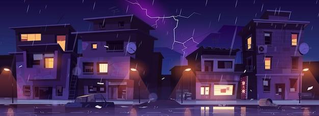 Rua do gueto à noite chuva com relâmpagos, favela arruinou prédios antigos abandonados inundados com chuva de água.