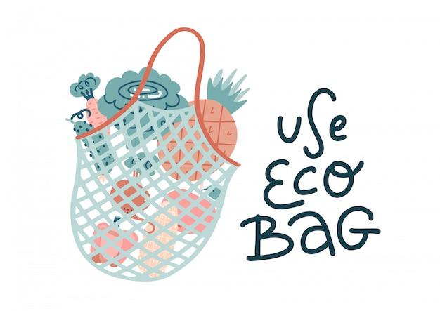 Saco de compras de malha preenchido com legumes frescos e frutas com letras de mão desenhada usar saco ecológico.