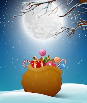 Saco de papai noel com presentes para crianças na neve