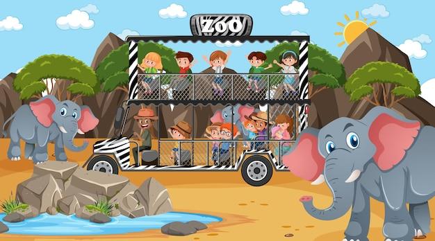 Safari durante o dia com muitas crianças observando o grupo de elefantes