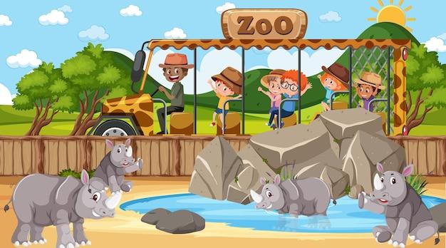 Safari durante o dia com muitas crianças observando o grupo de rinocerontes