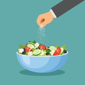 Salada grega em um prato. mão polvilha sal. conjunto de legumes frescos em uma tigela isolada sobre fundo azul.