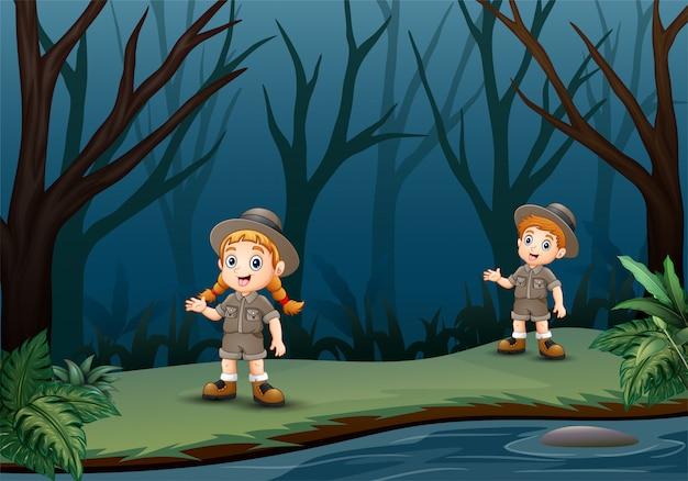 Scout menino e menina estão falando na floresta escura