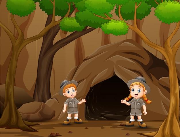 Scout menino e menina falando perto da caverna