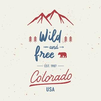 Selvagem e livre com letras de mão colorado. conceito de viagens com montanhas e respingos de aquarela abstratos.