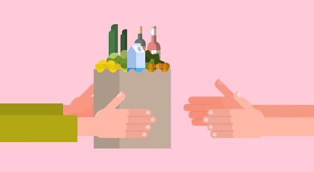 Serviço de entrega de mercearia com a mão, dando o saco de papel cheio de comida