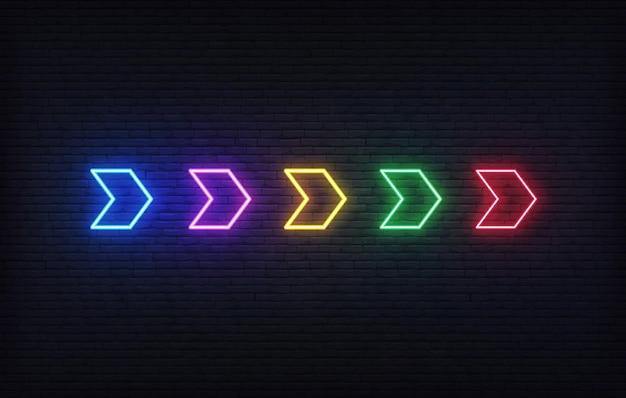 Seta de néon. conjunto de ponteiro de seta de néon brilhante futurista colorido no fundo da parede de tijolo.