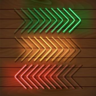Setas verdes, amarelas e vermelhas de néon em uma parede de madeira