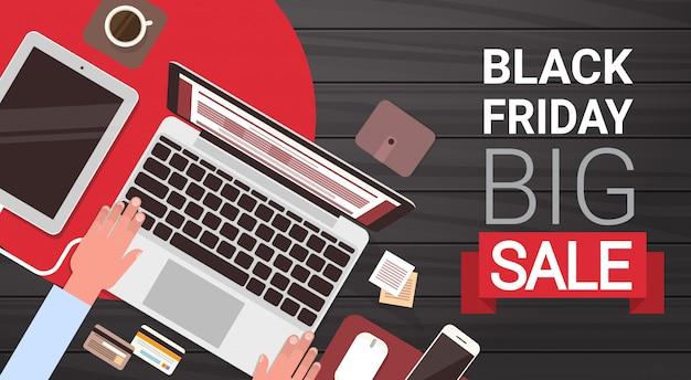 Sexta-feira negra grande venda banner design com mãos de homem, digitando no computador portátil acima vista