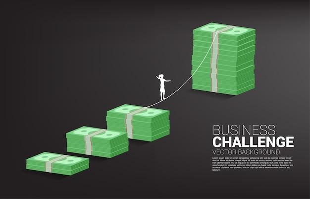 Silhueta da mulher de negócios que anda na maneira da caminhada da corda ao gráfico da pilha de notas de banco do dinheiro. conceito para o risco e o desafio comerciais.