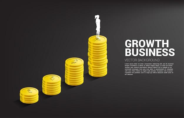 Silhueta da mulher de negócios que está sobre o gráfico do crescimento com a pilha de moeda.