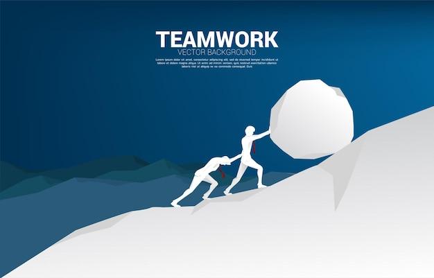 Silhueta de dois empresários empurrando a grande pedra para o topo da montanha. conceito de desafio empresarial e trabalho árduo.