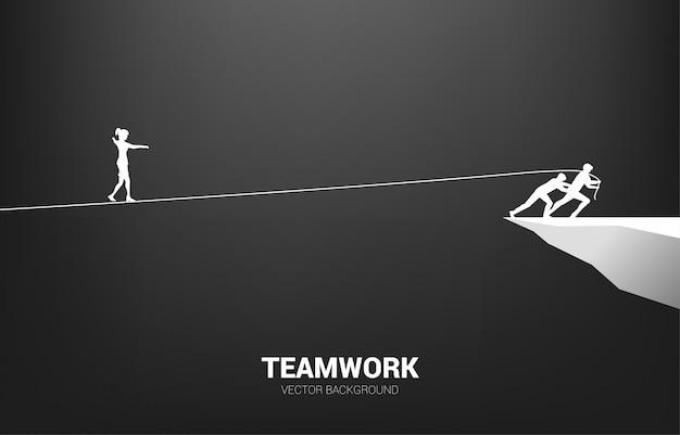 Silhueta de empresária andando na corda andar maneira puxada pela equipe. conceito de apoio ao trabalho em equipe e equipe ...