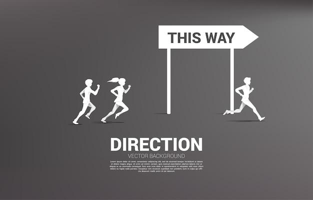 Silhueta de empresário e empresária correndo para com sinalização de direção. conceito de empresa de negócios e direção de equipe