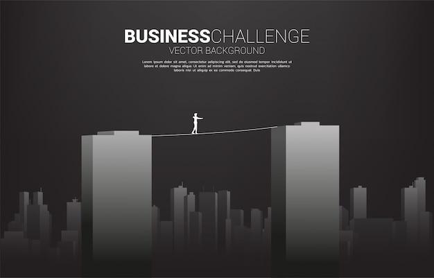 Silhueta, de, homem negócios, andar, ligado, corda, passeio, maneira, através, predios., conceito, para, risco negócio, e, desafio, em, carreira
