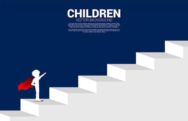 Silhueta de menino em super-herói no degrau da escada. conceito de início da educação e futuro das crianças.