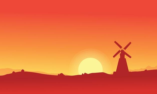 Silhueta de moinho de vento em fundo laranja