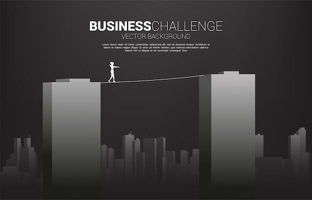 Silhueta de mulher de negócios andando na corda a pé através do edifício. conceito de risco de negócios e desafio na carreira