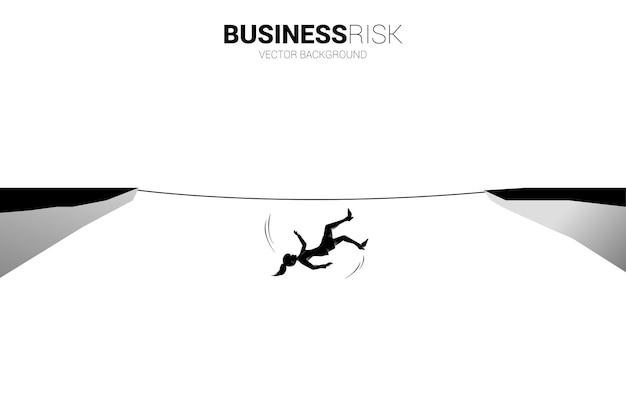 Silhueta de mulher de negócios caindo de uma caminhada pela corda. conceito de risco e falha do negócio