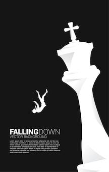 Silhueta de mulher de negócios caindo do xadrez rei.