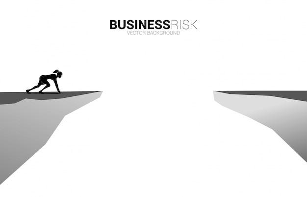 Silhueta de mulher de negócios pronta para correr para saltar sobre o fosso. conceito de risco de desafio de negócios.