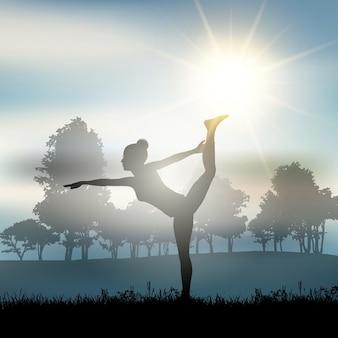 Silhueta de uma mulher em um pose da ioga em uma paisagem ensolarada