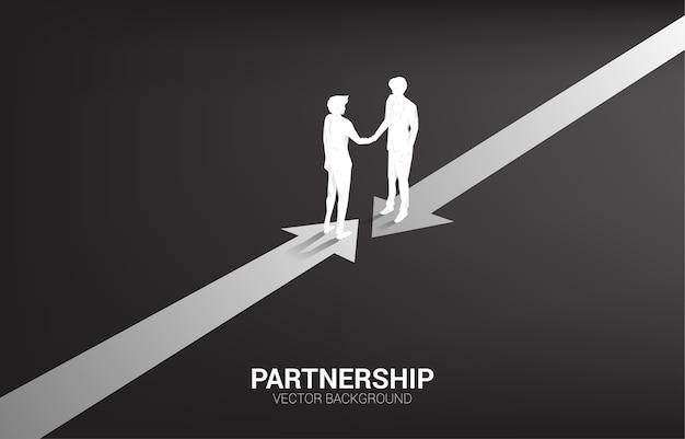 Silhueta do aperto de mão do empresário da seta de direção oposta. conceito de parceria e cooperação de trabalho em equipe.