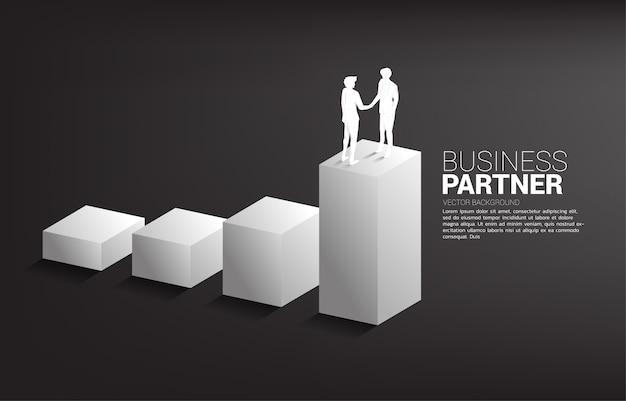 Silhueta do aperto de mão do empresário no crescente gráfico. conceito de parceria e cooperação de trabalho em equipe.
