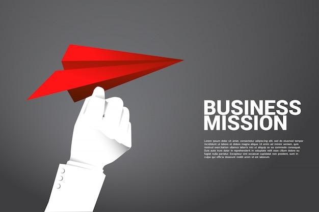 Silhueta do avião de papel do origâmi vermelho da preensão da mão do homem de negócios. conceito de negócio de iniciar negócios e empresário