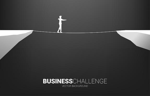 Silhueta do empresário andando na maneira de andar a corda. conceito de risco de negócios e desafio no plano de carreira