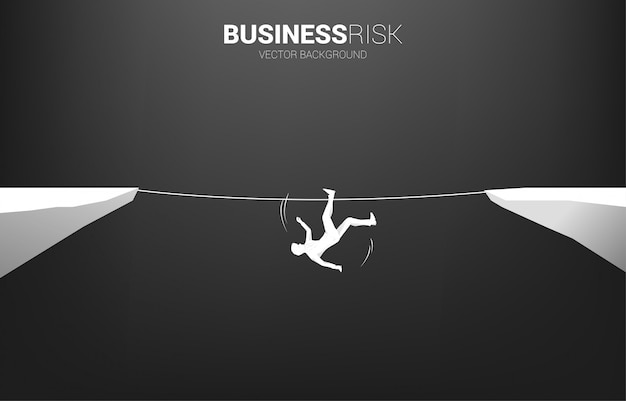 Silhueta do empresário caindo da maneira de andar a corda.