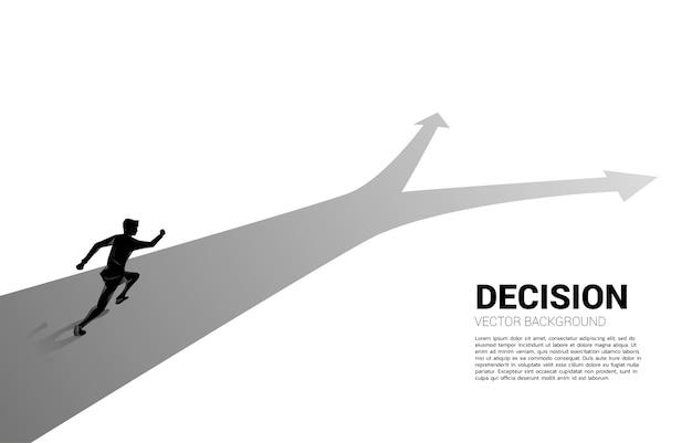 Silhueta do empresário correndo na encruzilhada. conceito de tempo para tomar decisões na direção dos negócios