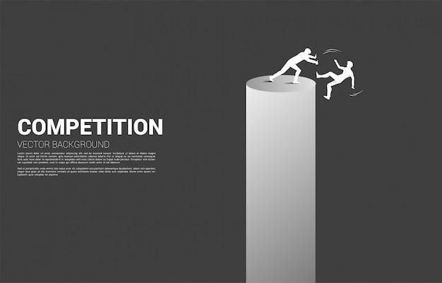 Silhueta do empresário empurrar o outro caindo da torre. conceito de concorrência empresarial e desafiante.