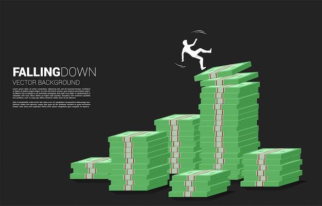 Silhueta do empresário escorregar e cair da pilha de notas de dinheiro. conceito de falha e negócios acidentais