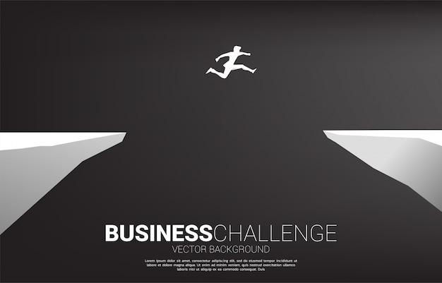 Silhueta do empresário saltando sobre a abertura do vale. conceito de risco de desafio de negócios.